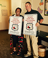 photo of two people each holding crime free sign