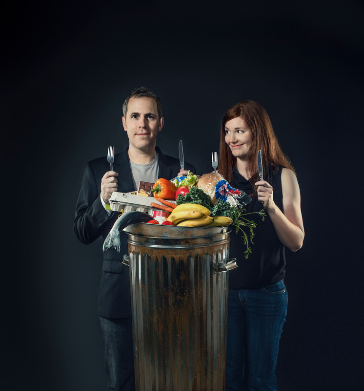Photo of two people holding a knife and fork infront of a garbage can full of food